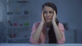 Douleur épuisée de femme du mal principal derrière la fenêtre pluvieuse, désordre de migraine banque de vidéos