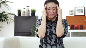 Douleur asiatique de sensation de femme sur l'oeil avec l'utilisation du t?l?phone portable ? la maison banque de vidéos