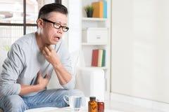 Douleur asiatique mûre de gorge d'homme Photos stock
