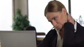 Douleur cervicale de sentiment de femme d'affaires travaillant sur l'ordinateur portable dans le bureau, problème spinal banque de vidéos