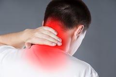 Douleur cervicale, homme souffrant du mal de dos sur le fond gris images stock