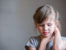 Douleur cervicale Le portrait a soumis à une contrainte la fille malheureuse d'enfant avec douleurs de dos, sentiment humain néga photographie stock