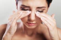 Douleur dans les yeux La jeune belle femme tient sa main devant ses yeux Douleur intense Le concept de la santé Sur un backgro gr photo stock