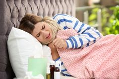 Douleur de femme de toux et froid dans le lit photo stock