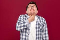 Douleur de gorge sur le froid Portrait d'homme âgé moyen dans la chemise occasionnelle et des lunettes à carreaux tenant et tenan images libres de droits