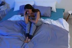 Douleur de jeune femme de l'insomnie à la maison bedtime photo stock