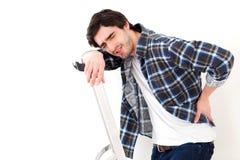 Douleur de jeune homme tout en travaillant à un escabeau Images stock