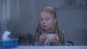 Douleur de petite fille de la grippe derrière la fenêtre pluvieuse éternuant et buvant du thé chaud banque de vidéos