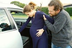 Douleur de sentiment de femme enceinte aidée pour entrer dans la voiture par l'ami Photographie stock libre de droits