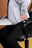 Douleur dorsale tout en fonctionnant au bureau Image stock