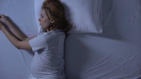Douleur enceinte de douleur de dame prenant la pilule se situant dans le lit, médicament d'effet secondaire banque de vidéos