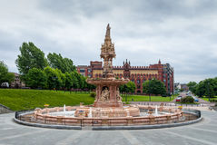 Doulton Fountain, Glasgow Green. The restored Doulton Fountain, Glasgow Green with Templetons Carpet Factory in the background Royalty Free Stock Photos