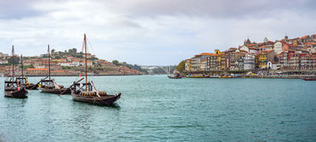 Douro river with rabelos boat and port wine barrels at Porto Oporto cityscape panorama Stock Photos