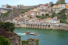 Douro river with tourist boat and Porto Oporto downtown viewed from romantic church ruins Stock Photos