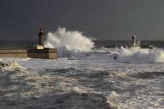 Douro storms. Stormy sunset at the harbor of the mouth of the river Douro, in Porto, Portugal, with big waves against old lighthouse, new pier and beacon Royalty Free Stock Image