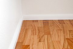 Doussie parquet floor. With reddish surface and white walls Royalty Free Stock Photo