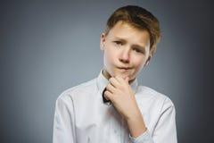 Doute, expression et concept de personnes - garçon pensant au-dessus du fond gris photo stock