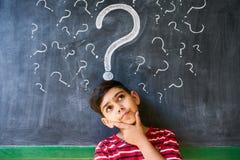 Doutes et points d'interrogation avec l'enfant pensant à l'école Photographie stock libre de droits