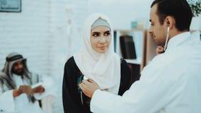 Doutor árabe Checking Heartbeat uma mulher muçulmana imagens de stock