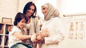 Doutor árabe Giving Toy a pouco paciente bonito fotos de stock royalty free