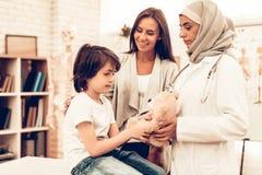 Doutor árabe Giving Toy a pouco paciente bonito Doutor fêmea muçulmano seguro Criança no pediatra Conceito do hospital fotografia de stock royalty free