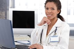 Doutor étnico de sorriso com laptop foto de stock