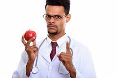 Doutor africano novo do homem que guarda a maçã vermelha ao apontar o dedo fotos de stock