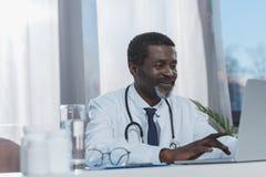doutor afro-americano de sorriso que trabalha com portátil Foto de Stock