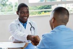 Doutor afro-americano que dá boas-vindas ao paciente fotos de stock