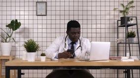 Doutor afro-americano que guarda texting esperto do telefone video estoque