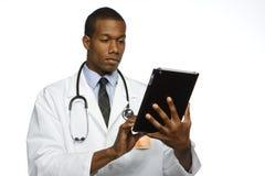 Doutor afro-americano que usa a tabuleta eletrônica, horizontal Imagens de Stock