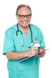 Doutor alegre que recolhe a informação do paciente Fotos de Stock