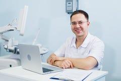 Doutor alegre que senta-se no escritório do ` s do doutor com portátil imagem de stock royalty free