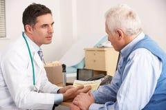 Doutor americano que fala ao homem na cirurgia Foto de Stock Royalty Free