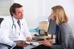 Doutor americano que fala ao paciente da mulher de negócios Fotos de Stock