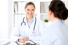 Doutor amigável e paciente de sorriso que sentam-se na tabela Conceito do serviço médico da notícia muito boa e do nível elevado foto de stock