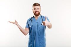 Doutor amigável feliz do homem que apresenta o copyspace em sua palma foto de stock