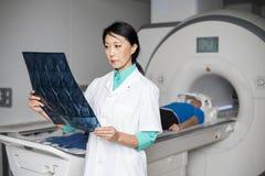 Doutor Analyzing Raio X Quando Paciente que encontra-se na máquina da varredura do CT Imagens de Stock