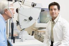 Doutor ao lado do equipamento para detectar a glaucoma Fotografia de Stock Royalty Free