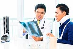 Doutor asiático que mostra a fotografia de raio X Foto de Stock Royalty Free