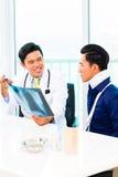 Doutor asiático que mostra a fotografia de raio X Imagens de Stock Royalty Free