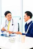 Doutor asiático que mostra a fotografia de raio X Foto de Stock