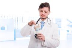 Doutor atrativo que retira euro do copo de café Fotografia de Stock