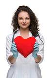 Doutor bonito da mulher que guarda um coração vermelho Fotografia de Stock Royalty Free