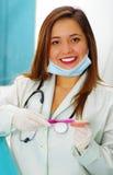 Doutor bonito da mulher que levanta para a câmera usando uma máscara da cirurgia em seu queixo quando escovar uma chapa dental fa foto de stock