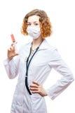 Doutor bonito do ruivo no revestimento do laboratório com a seringa na máscara Foto de Stock Royalty Free