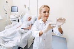 Doutor capaz escrupuloso que guarda com cuidado uma seringa Fotos de Stock
