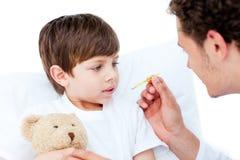 Doutor caucasiano que toma a temperatura do rapaz pequeno Foto de Stock Royalty Free