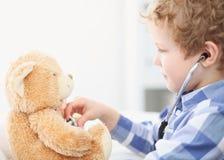 Doutor Checking da criança a pulsação do coração de um Teddy Bear Fotos de Stock