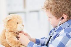 Doutor Checking da criança a pulsação do coração de um Teddy Bear Imagens de Stock Royalty Free